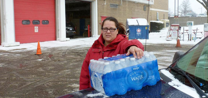"""Rabecka Cordell picks up a case of bottled water outside the fire station in Flint, Mich. """"We both have lead poisoning,"""" said Cordell. She says she has leukemia and her son has learning and speech disabilities. She will not even bathe in Flint water and won't wash her son in it. (AP photo)"""