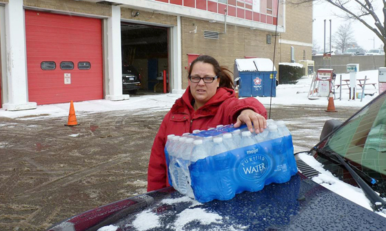 "Rabecka Cordell picks up a case of bottled water outside the fire station in Flint, Mich. ""We both have lead poisoning,"" said Cordell. She says she has leukemia and her son has learning and speech disabilities. She will not even bathe in Flint water and won't wash her son in it. (AP photo)"
